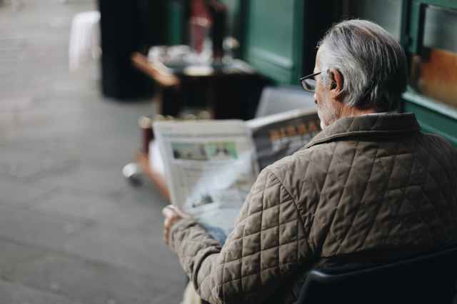 man sitting reading newspaper