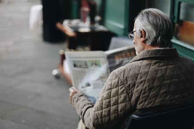 man sitting reading newspaper